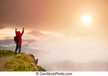 Young man with backpack standing  on top of  mountain watching the sunrise