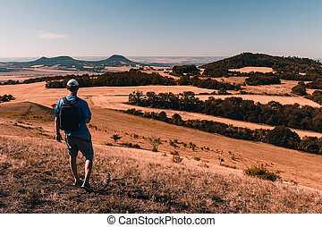 Young man with backpack walking down from hill and looking to Czech central mountain valley at sunrise