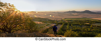 Young man with backpack walking down from hill and looking to Czech ore mountain valley at sunrise. Czech landscape