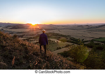 Young man with backpack walking down from hill and looking to Czech ore mountain valley at sunrise landscape