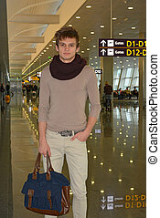 Young man with bag standing in airport hall