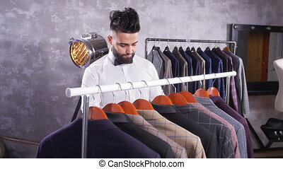 Young man with beard choosing suit in a shop