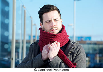 Young man with beard posing with scarf outdoors
