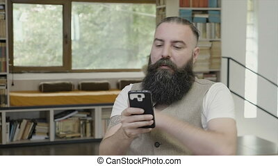 Young man with beard reading something on his smartphone and...