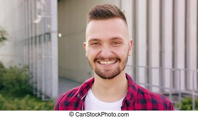 Young Man with Beard Smiling in Town