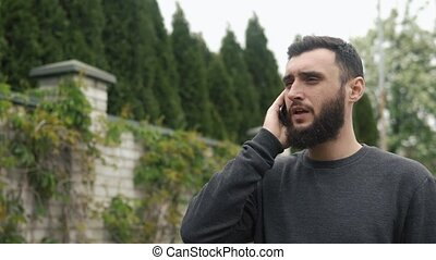 young man with beard talking on the phone near his country house, motion camera