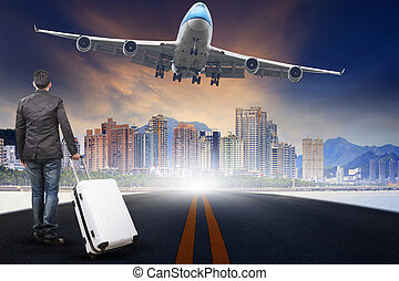 young man with belonging luggage standing against urban scen an