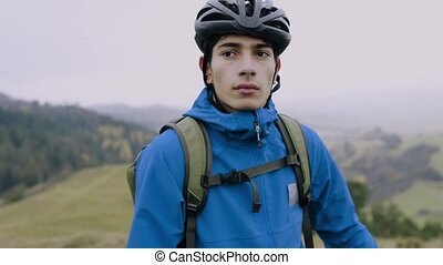 Young man with bicycle outside in autumn nature.