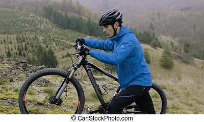 Young man with bicycle outside in autumn nature. - Young...