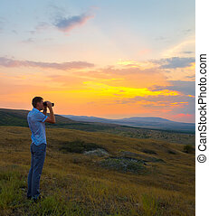 Young man with binoculars in the mountains at sunset
