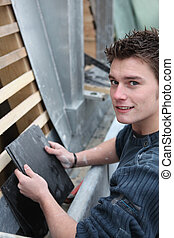 Young man with bitumen roof tiles