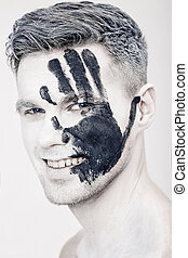 Young man with black hand print on white face. Closeup...
