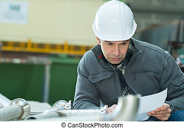 young man with blueprints working in a factory