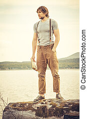 Young Man with book standing outdoor with lake on background Summer vacations and Lifestyle concept retro colors