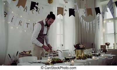 Young man with bow and vest setting a table for an indoor...