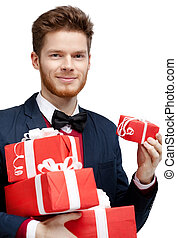 Young man with bow tie carries a lot of presents