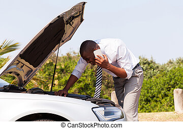 young man with broken down car calling for help