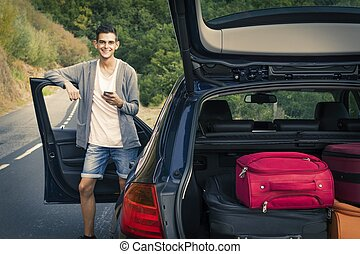 young man with car with suitcases and mobile phone,...