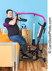 Spastic young man with infantile cerebral palsy from birth complications using a patient lift to transfer from a healthcare bed to his wheelchair giving the camera a happy friendly smile