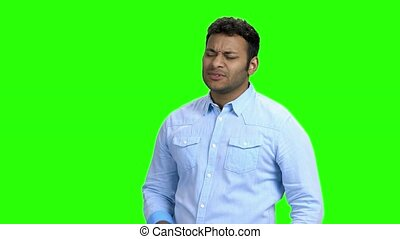 Young man with chest pain on green screen. Indian guy suffering from heart ache on Chroma Key background. Health problem concept.
