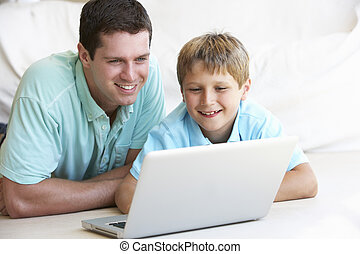 Young man with child on laptop computer
