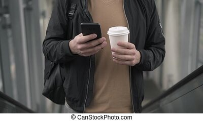 Young man with coffee and smartphone on escalator