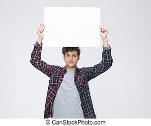 Young man with curly hair holding blank billboard