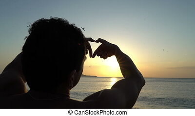 Young man with curly hair making heart with his hands at amazing sunset on the beach. Silhouette of dreamer. Art inspiration and beautiful light.