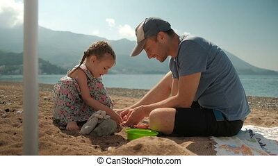 Young man with daughter sits on beach in summer day.