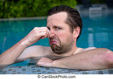 young man with disgust on his face pinches nose, something stinks, very bad smell in swimming pool because of chloride.