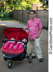 young man with double pram and two kids in it, twins