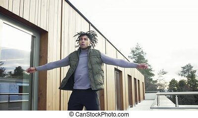 Young man with dreadlocks doing exercise outdoors on terrace...