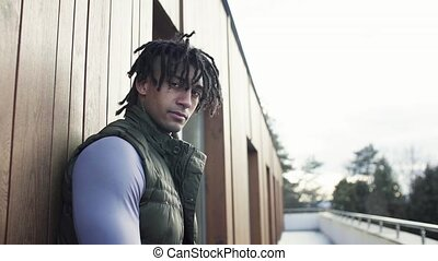 Young man with dreadlocks standing outdoors on terrace, ...