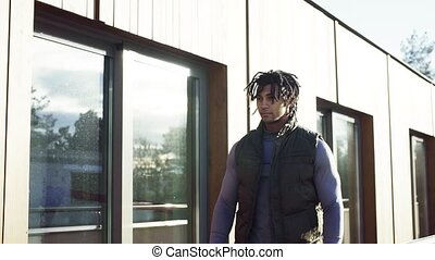 Young man with dreadlocks walking outdoors on terrace. Slow ...