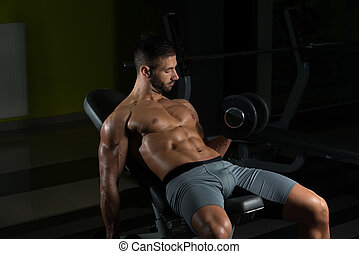 Young Man With Dumbbell Exercising Biceps