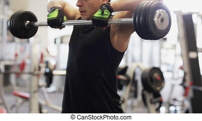 sport, bodybuilding, lifestyle and people concept - young man with dumbbell flexing muscles in gym