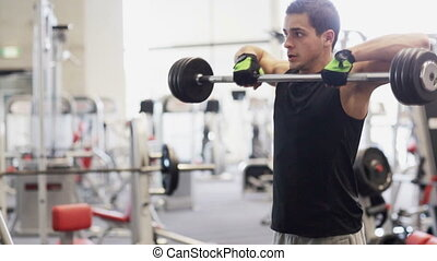 young man with dumbbell in gym