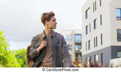 young man with earphones and backpack in city - technology, ...