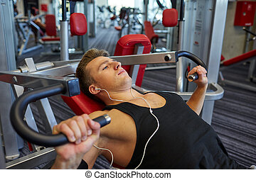 young man with earphones exercising on gym machine - sport, ...