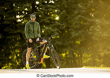 Young man with ebike, mountain bike with electric battery in...