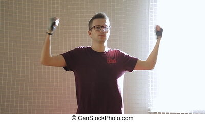 Young man with eyeglasses in red t-shirt does exercise in...