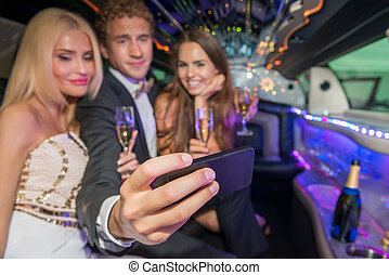 Young man with female friends taking selfie on mobile phone in limousine