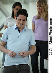 Young man with friends walking down stairs