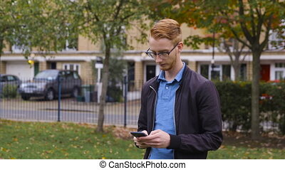 Young man with ginger hair makes a call in a park