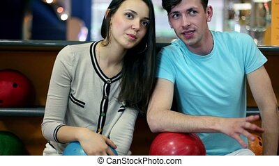 Young man with girl talk and laugh in bowling club, close up...