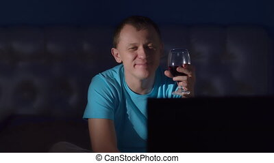 Young man with glass of red wine watching tv at night, recreation concept