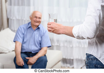 Young man with glass of water near grandfather