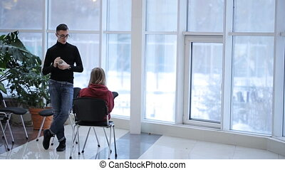 Young man with glasses and a black pullover, talking to a classmate on background of panoramic windows at university.