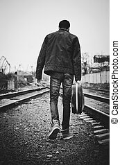 A young man with guitar case in hand is going away. Rear view, black and white