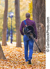 Young man with guitar walking in park